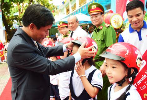 Phó Chủ tịch UBND tỉnh Nguyễn Văn Phương trao tặng mũ bảo hiểm cho các em học sinh