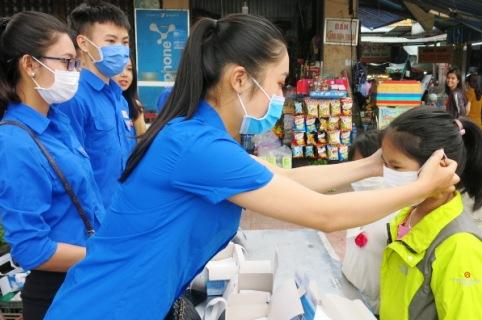 Các đoàn viên, thanh niên huyện Phong Điền đeo khẩu trang cho các em nhỏ tại chợ Phò Trạch thị trấn Phong Điền