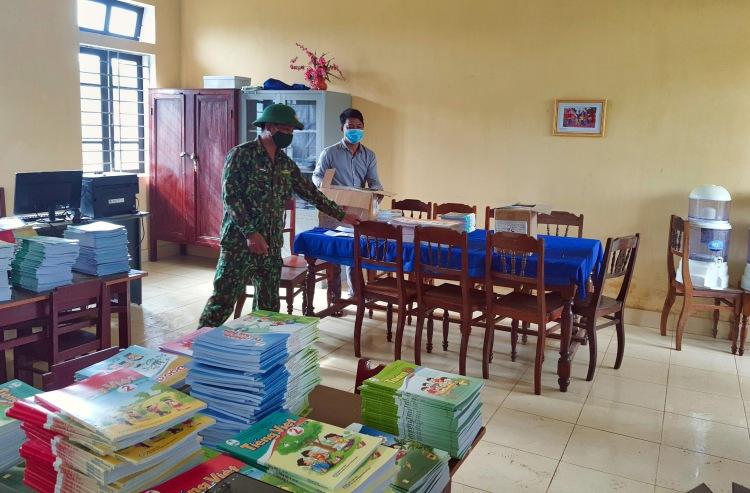 Cán bộ, chiến sĩ Đồn biên phòng cửa khẩu A Đớt phối hợp cùng nhà trường chuẩn bị sách vở cho các em học sin